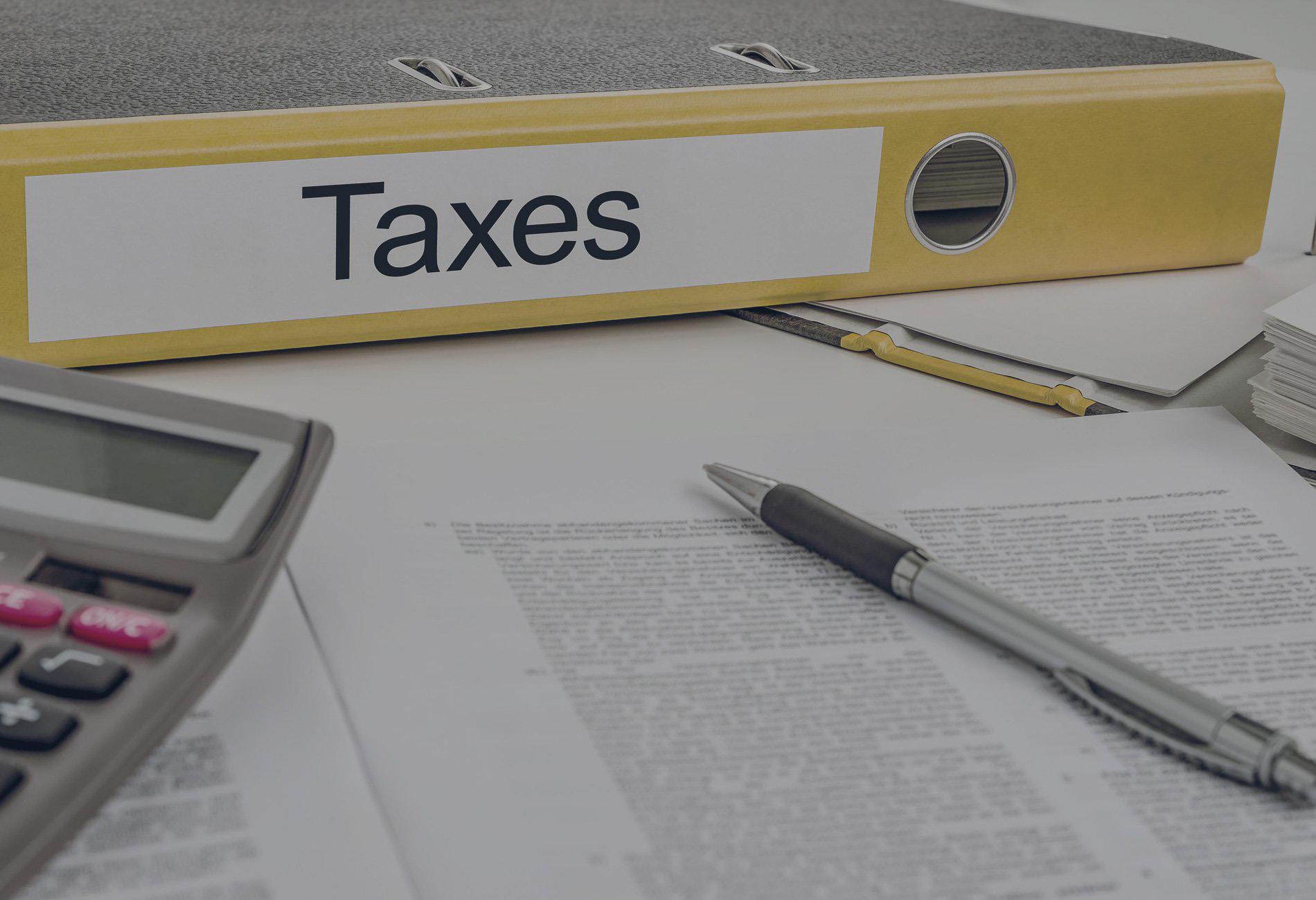 File of taxes on table with calculator and pen